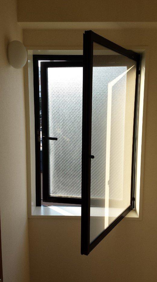 階段室 「たて滑り出し窓(外開き)」(開いた状態)。網戸は内側に開く必要があり、インプラスを取り付けるには、網戸をロール網戸に取り換える必要があります。