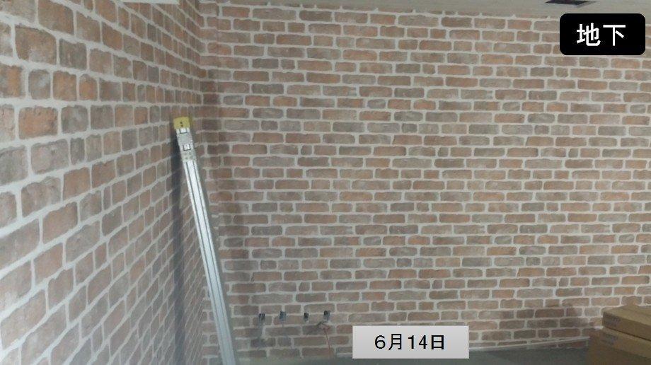 地下室のリノベーション中 /写真。レンガ模様の壁紙が貼られました。