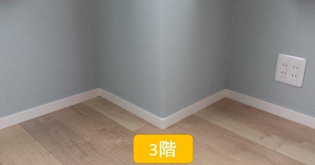 白いプラスティック巾木(木目フローリングと水色壁紙の間)